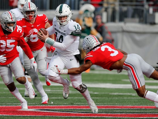 Michigan State quarterback Brian Lewerke, center, runs
