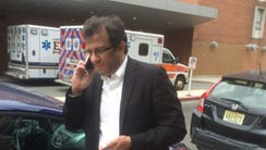 Shahid Qureshi on the phone outside Carepoint Health
