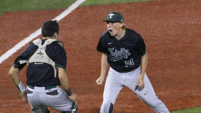 Trinity's Max Medley (14), right, celebrated after closing out the win against St. X during the 7th Region Championship at Patterson Stadium. 