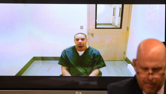 Olvy Torres is seen on a TV screen during his arraignment at the Hudson County Central Judicial Processing Court in Jersey City.
