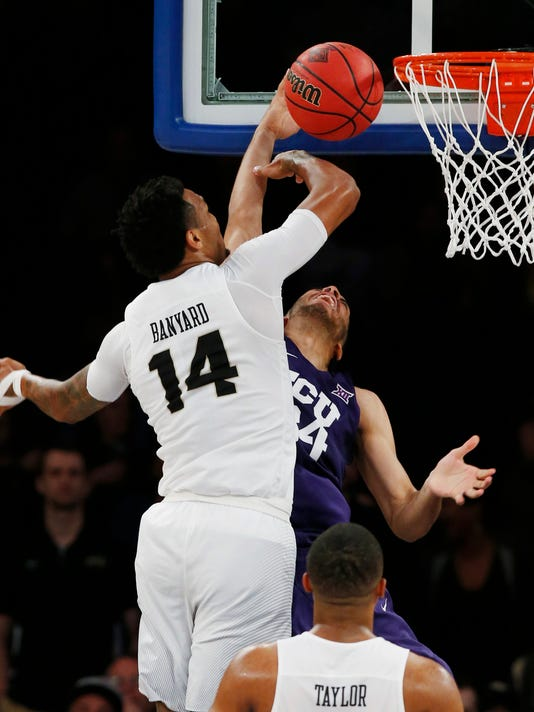 Central Florida's Nick Banyard (14) defends TCU's Kenrich Williams (34) during the first half of an NCAA college basketball game in the semifinals of the NIT Tuesday, March 28, 2017, in New York. (AP Photo/Kathy Willens)