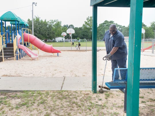 Pensacola Parks and Recreation Department employee Larry Crenshaw trims weeds at Morris Court Park after the park reopened on Tuesday, May 30, 2017.