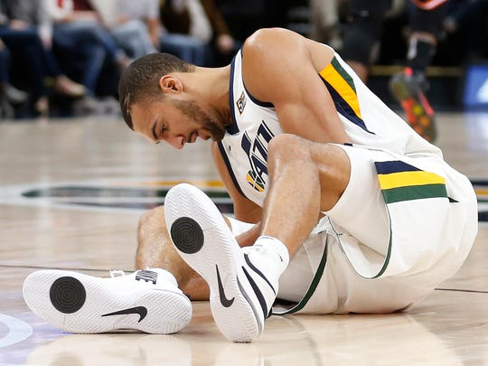 Utah Jazz center Rudy Gobert grabs his knee after being injured in the second half Friday.