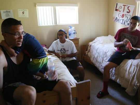 Randy Roy (left) speaks to his cousins, Tayler and Tyler Hawkins, about college during the Roy family reunion.