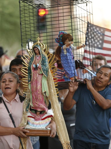 Gina Sanchez carries the Virgin Mary while she sings as over 100 people march to ICE's Enforcement and Removal Operations Field Offices during a Rally for Migrants in Phoenix, Ariz. on June 17, 2018.