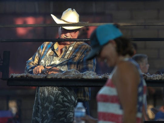 Duane Baker cooks food Tuesday during the annual Anderson
