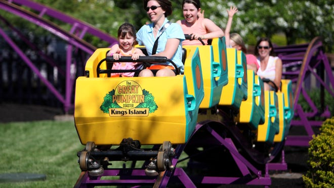 """Taking their chances in the front and second seats, the Banks family, Grayce, 5, Christal, and Peyton, 10, of Mason, enjoyed their ride on The Great Pumpkin Coaster inside of Kings Island's redesigned kid's area """"Planet Snoopy"""" on Wednesday, April 14, during a family preview night."""