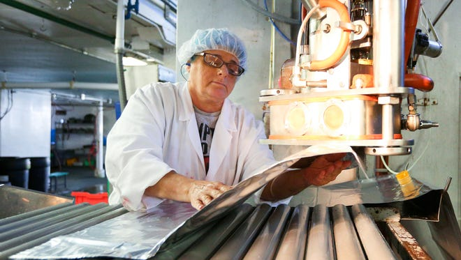 Oregon Fruit Products employee Gail Messina runs the aseptic filler that places 42-pounds of fruit puree into a bag that is used in brewing,