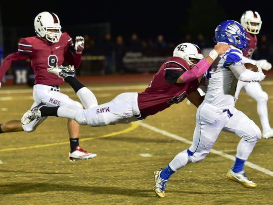 Milford's Christian Koschke (middle) tries to bring