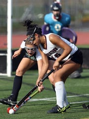 Ridge's Hannah Ingal and Morristown's Olivia Graham battle for the ball in a NJSIAA North 1 Group IV  field hockey semifinal.