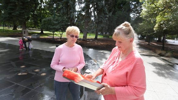 Charlotte King, right, meets with Mary Fisher at the World War II Memorial on Thursday, Sept. 17, 2015, in Salem, Ore. Fisher found a World War II service flag at a rummage sale with names handwritten next to three blue stars. King is the daughter of Grant Bowder, one of three brothers honored on the flag. Fisher returned the flag to King and her family.