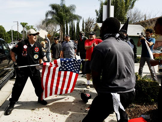 """A Ku Klux Klansman, left, uses an American flag to fend off angry counter protesters after members of the KKK tried to start a """"White Lives Matter"""" rally at Pearson Park in Anaheim, Calif., on Saturday, Feb. 27, 2016. The event quickly escalated into violence and at least two people had to be treated at the scene for stab wounds."""