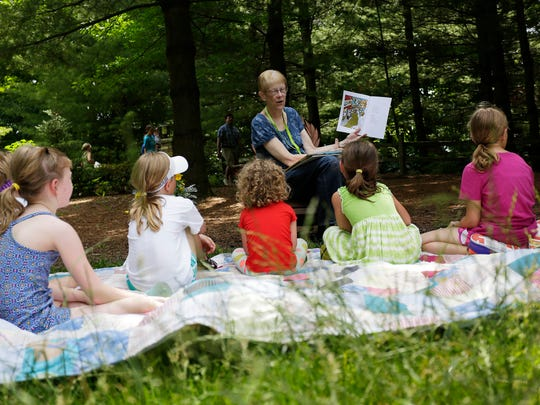 Story teller Linda Seider reads a book to children at Bookworm Gardens Thursday July 6, 2017 in Sheboygan, Wis.