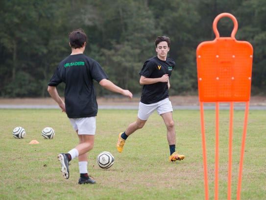 The boys soccer team run a drill during practice at