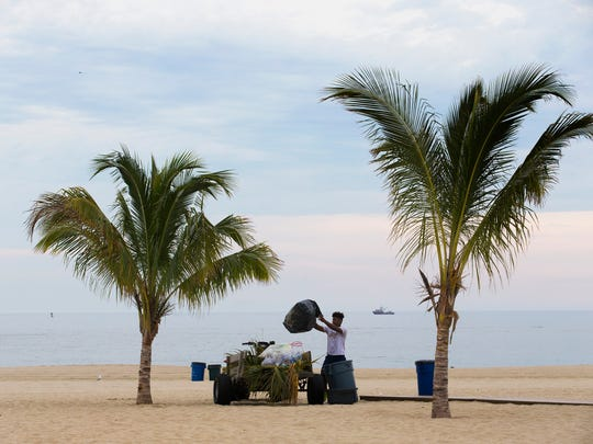 Bryce Bradford, of Neptune, empties the filled garbage cans as the beach at Jenkinson's is cleaned up for another day.