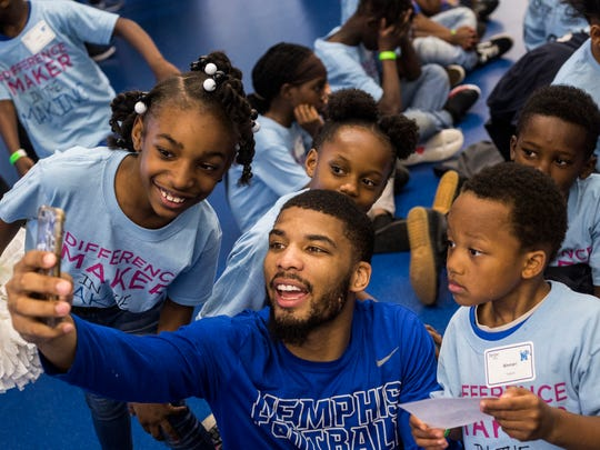 """April 28, 2018 - Roderick Proctor, a graduating senior who played on the Memphis football team, takes a selfie with kids during the Ashley HomeStore and the Memphis Tigers """"Hope to Dream"""" event at the Billy J Murphy Athletic Complex. 100 children received an entire bed set at the event."""