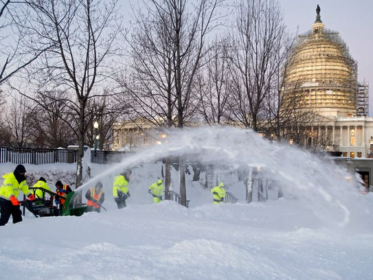 Employees of the Architect of the Capitol clear snow