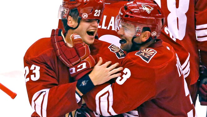 Arizona Coyotes defenseman Oliver Ekman-Larsson (23) celebrates with Keith Yandle (right) after his goal with 14 seconds left in overtime beat the Los Angeles Kings 3-2 Saturday, Oct. 11, 2014.
