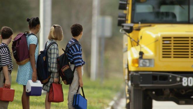 School children standing in line outside the school bus
