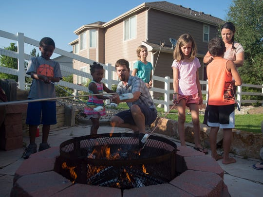 Jed Link huddles around a fire pit to roast marshmallows with neighbors and family friends in the backyard on Tuesday, July 11, 2018.