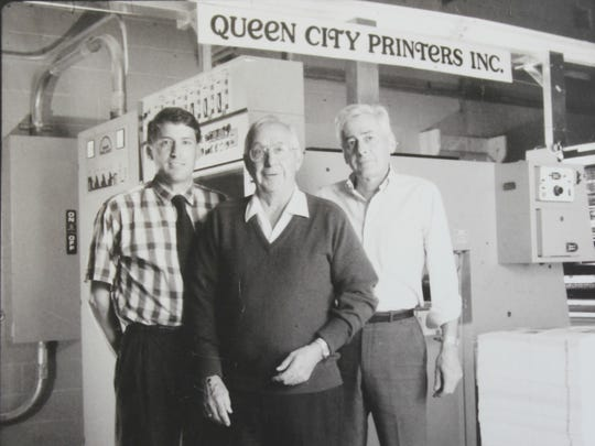 Dick Schillhammer, center, and his sons Alan, left, and John, right pose for a photo with Queen City Printers' first six-color press in 1990.