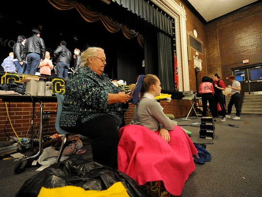 Theater Director Becky Fly, left, adjusts a ribbon