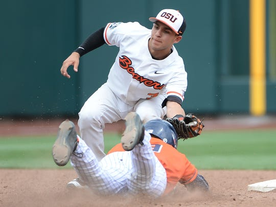 Oregon State Beavers infielder Nick Madrigal tags Cal State Fullerton Titans infielder Dillon Persinger on Saturday omn the way to the Beavers' win.