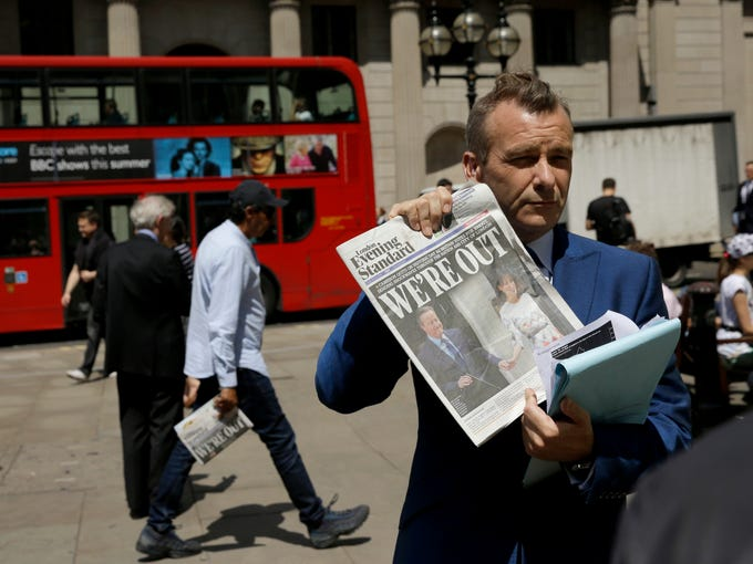 A journalist holds up a copy of the London Evening