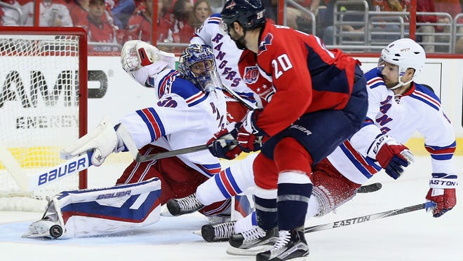 Rangers goalie Henrik Lundqvist makes one of his 42 saves, just getting a toe on Troy Brouwer's first-period attempt Sunday night in Game 6 at Washington.