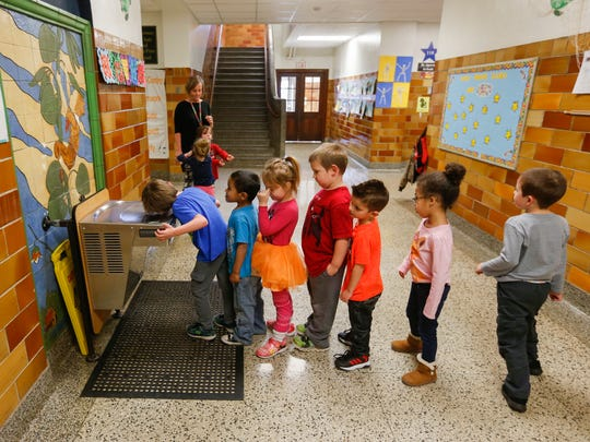 Students in Sarah Fox's Wonder Years preschool class at Bowerman Elementary School stop by the water fountain after indoor recess on Wednesday, Feb. 7, 2018.