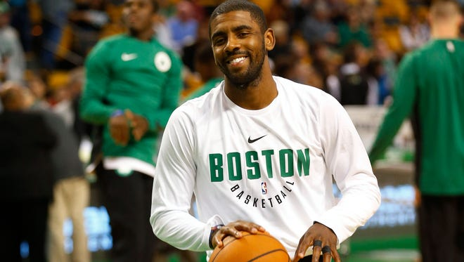 Boston Celtics guard Kyrie Irving (11) smiles as he warms up prior to their preseason game against the Charlotte Hornets at TD Garden.