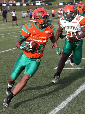 Dock Luckie-makes a reception while Ellrie Allen pursues during FAMU's scrimmage Saturday.