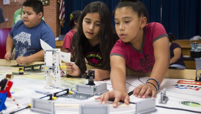 Amy Rodriguez (left), 9, and Nizhoni Lopez, 9, map out a robotics challenge course at Hartford Sylvia Encinas Elementary School in Chandler on Saturday, Sept. 17, 2016.