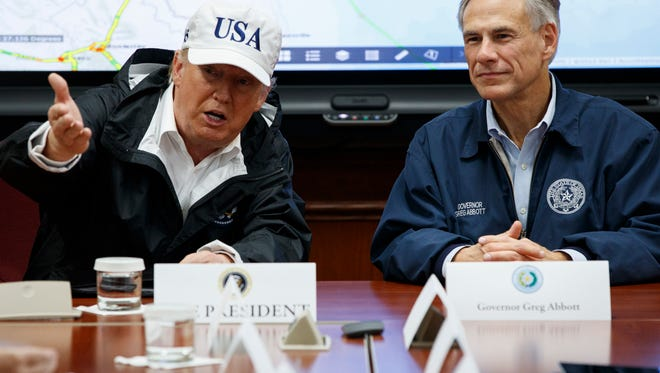 """President Trump, accompanied by Texas Gov. Greg Abbott, speaks during a briefing on Hurricane Harvey relief efforts on Aug. 29, 2017, at the the Texas Department of Public Safety Emergency Operations Center in Austin, Texas. The two have tried to crack down on so-called """"sanctuary cities"""" but been rebuffed by federal judges."""