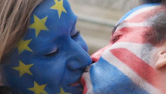 A couple with their faces painted in the flags of the European Union and Great Britain kiss in front of the Brandenburg Gate in Berlin on June 19, 2016.