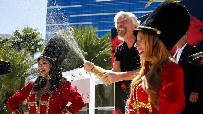Virgin Group founder Richard Branson sprays champagne at a news conference Friday, March 30, 2018, in Las Vegas where Virgin Hotels announced that it had bought the Hard Rock hotel and casino in Las Vegas.