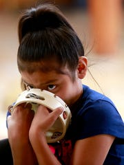 Tiana Tom, 9, of Red Rock, takes part in a class through