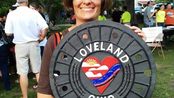 Bonnie McNett displays one of the ceramic Loveland manhole covers created by potter, ceramic artist and founder of Whistle Stop Clay Works Tim O'Grady.