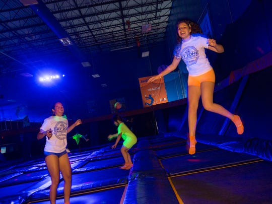 Syann Colon, 17, and Olivia Passalacqua, 16, both of Manchester, play on the trampolines during a GLOW session at Sky Zone in Lakewood.