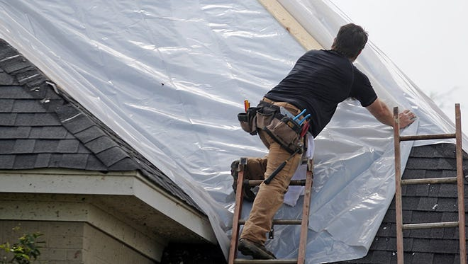Workers patch a roof in northeast Louisville, Miss. after many homes sustained damage in Monday's tornado.