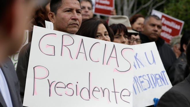 Sebastian Montalvan, left, who has been living in the country illegally, joined dozens of others who are here illegally, as well as activists and supporters to celebrate President Barack Obama's executive action on illegal immigration, at a at a news conference in Sacramento, Calif., Friday, Nov. 21, 2014.