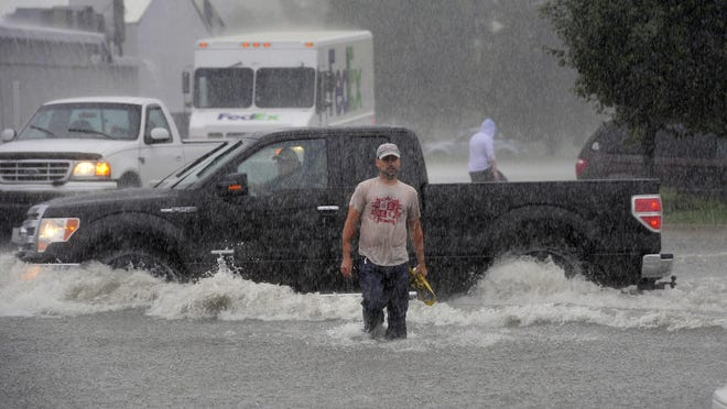 Chris Adelman walks through deep water and steady rain to help tow a car stuck in the flooded roadway on West Saginaw in Delta Township on Monday. A fast moving storm drenched the Lansing area.