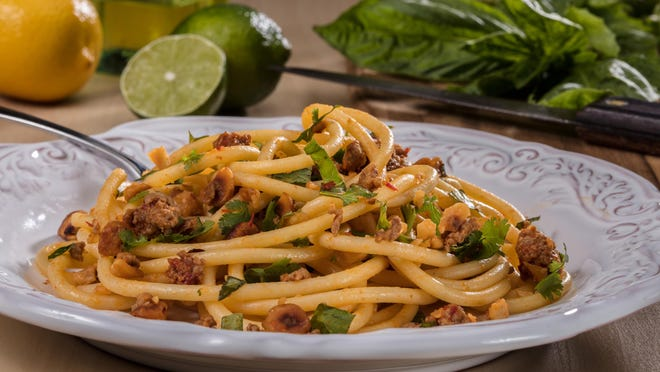 Bucatini, a long, spaghetti-like noodle with a hole running through the length of it, is tossed with hazelnuts, red pepper paste, lamb and fresh herbs.