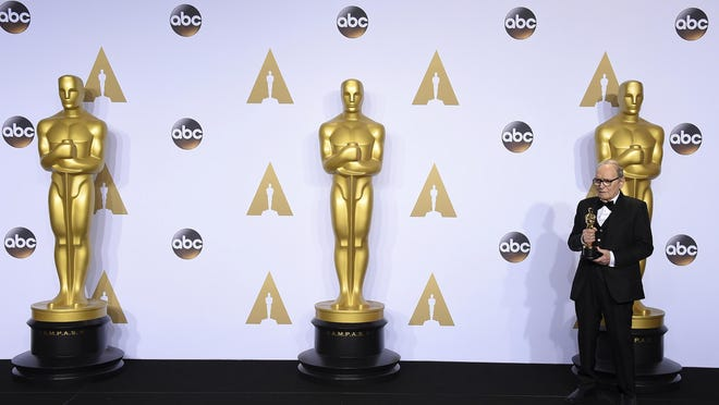 """FILE - In this Sunday, Feb. 28, 2016 file photo, Ennio Morricone poses in the press room with the award for best original score for """"The Hateful Eight"""" at the Oscars at the Dolby Theatre in Los Angeles. Morricone, who created the coyote-howl theme for the iconic Spaghetti Western """"The Good, the Bad and the Ugly"""" and the soundtracks such classic Hollywood gangster movies as """"The Untouchables,"""" died Monday, July 6, 2020 in a Rome hospital at the age of 91."""