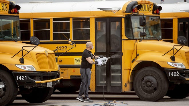 A man is shown in March disinfecting a school bus at an Austin school district bus terminal on Ernest Robles Way in Sunset Valley.