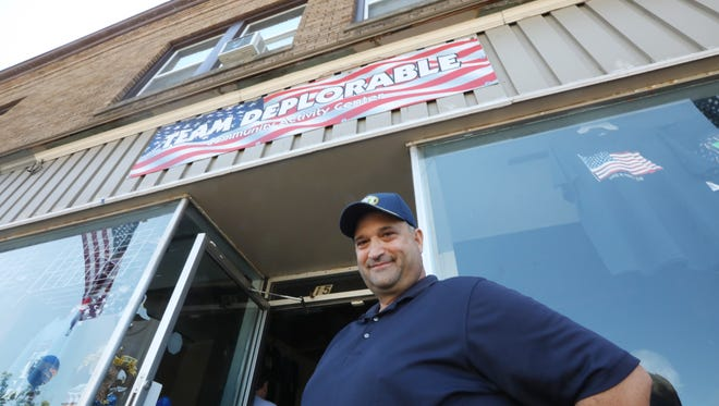 Bruce Ben-Dov outside his new T-shirt shop, Trump's Team Deplorable Community Activity Center, on Main Street in Webster on Wednesday, July 4, 2018.