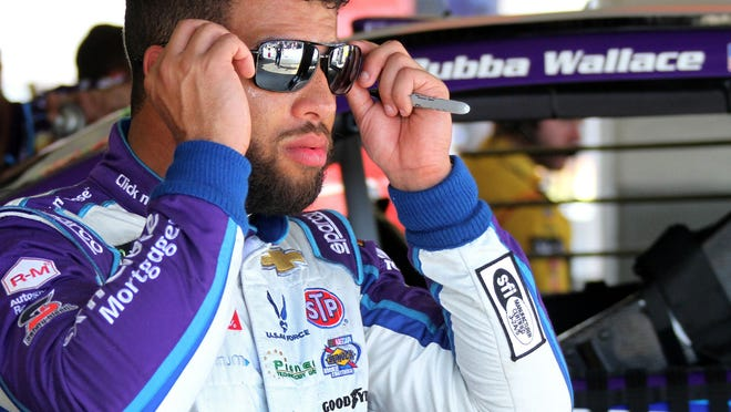 Bubba Wallace slips on his sunglasses as he walks out the garage for the No. 43 Chevrolet Camaro, Saturday February 10, 2018 during Cup practice at Daytona International Speedway.