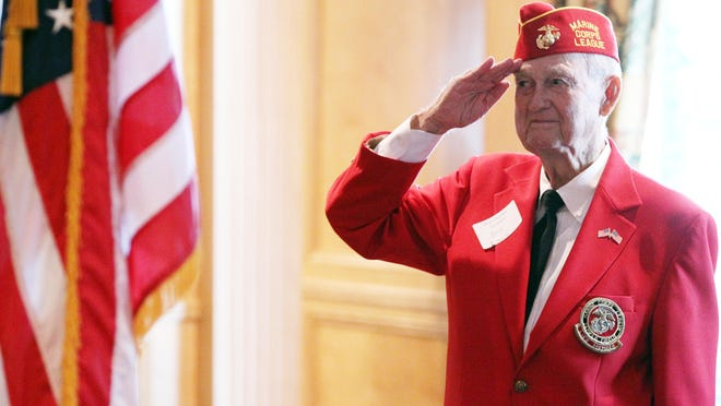 Bob Lowe, a veteran who survived the attack at Pearl Harbor in 1941, salutes during the singing of the national anthem during a reunion for Pearl Harbor survivors at the Petroleum Club Sunday, December 7, 2014, the 73rd anniversary of the attack, in Lafayette, La.