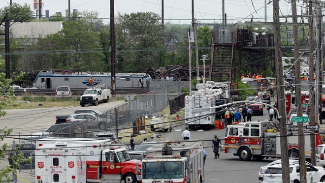 Emergency and transportation personnel work at the scene of a deadly train wreck, Wednesday, May 13, 2015, in Philadelphia. Federal investigators arrived Wednesday to determine why an Amtrak train jumped the tracks in Tuesday night's fatal accident.