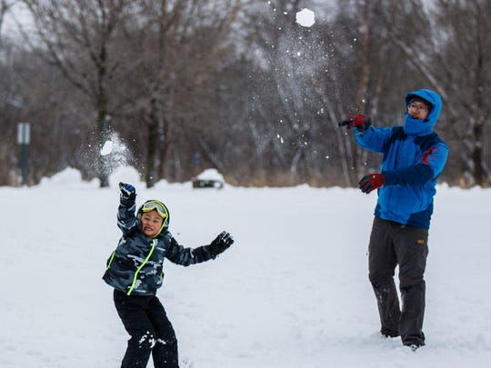 Dixon Mi and his son Kevin, 6, of Brookfield partake in a snowball fight at Mitchell Park in Brookfield on Sunday, April 15, 2018. A weekend storm covered the area with ice and snow luring residents outside to play.